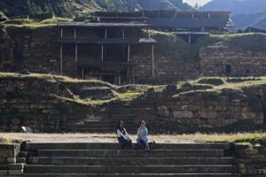 Image of the archaeological site of Chavin de Huantar with research assistants Antonella Rivera Tames and Carly Rose Lacoste seated on steps
