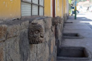 An image of imitation tenon heads adorning the wall of a house in Chavin